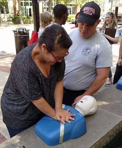 Woman practicing hands-only CPR during a training session in Greenville.
