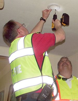 Volunteer installing a smoke alarm in a Greenville home
