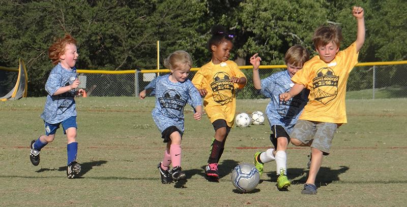 a group of kids running down a soccer field at Holmes Park