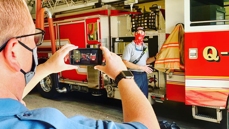 fire personnel filming fire fighter using cellular phone